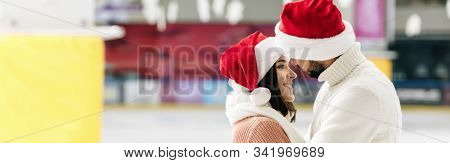 Panoramic Shot Of Beautiful Happy Couple In Santa Hats Spending Christmastime On Skating Rink
