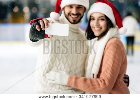 Selective Focus Of Happy Couple In Santa Hats Taking Selfie On Smartphone On Skating Rink At Christm