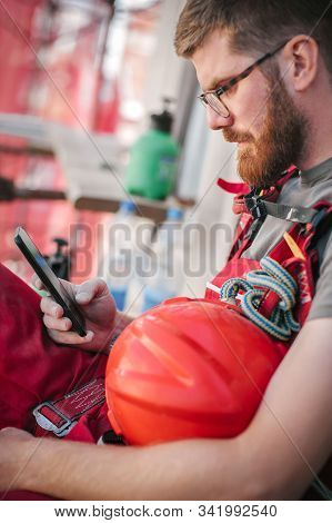 Building Site Worker Sitting High On The Scaffolding, Resting And Using Mobile Phone