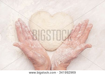 Womens Hands, Flour And Dough. A Woman Is Preparing A Dough For Home Baking. Holding A Heart Shaped