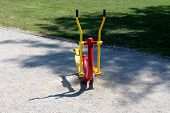 Front view of elliptical cross trainer colorful red and yellow public park fitness outdoor exercise equipment surrounded with gravel and freshly cut grass in local public park poster
