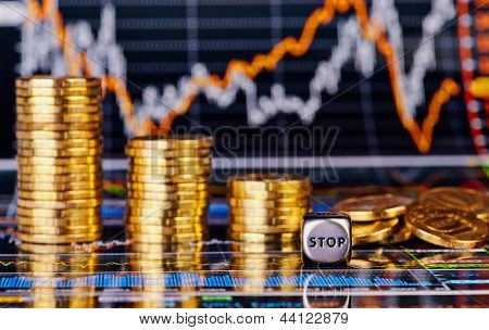 Downtrend Golden Coins Stacks, Dices Cube With The Word Stop And Financial Chart As Background. Sele