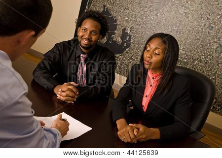Young African American couple about to sign papers