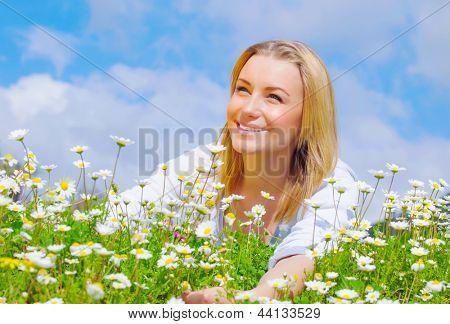 Pretty woman lying down on daisy field, cute female enjoying little white spring time flowers, having fun outdoors