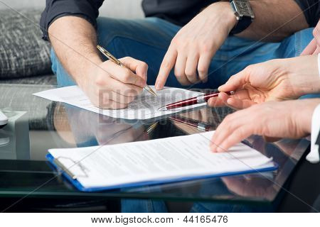 Two people signing a document