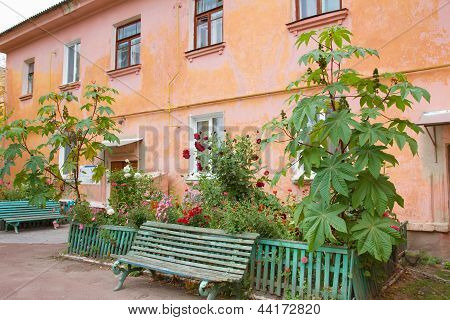 Green Bench In Frond Of An Old House