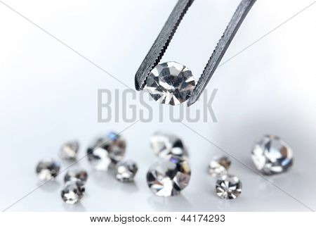 Beautiful shining crystal (diamond) in the tweezers, isolated on white
