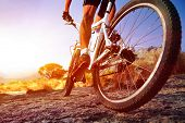 low angle view of cyclist riding mountain bike on rocky trail at sunrise poster