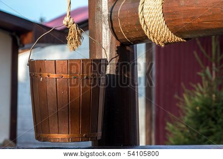 Wooden well. Bucket on a rope