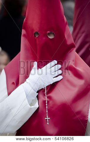 Penitent with a rosary in his hand in a procession on Holyweek