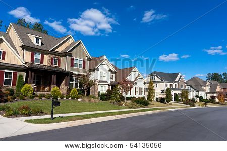 Street of large suburban homes on sunny day poster