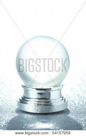 Empty snow globe on glittering background