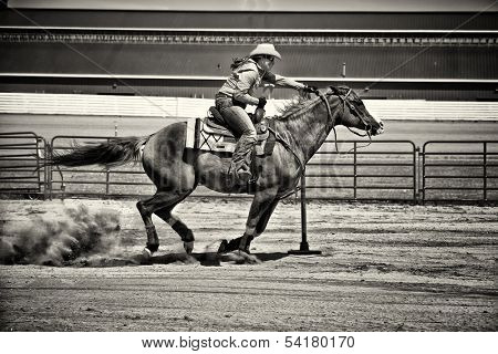 Western horse and rider competing in pole bending and barrel racing competition. Gritty look with sepia toning. poster