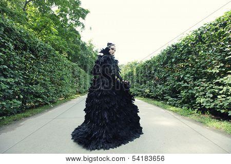 Dark Queen in park. Fantasy black dress.
