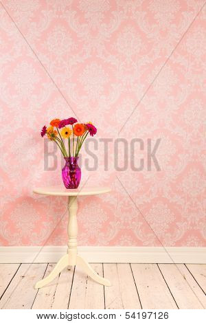 Vintage wall, wooden floor and plinth with white table and vase with flowers