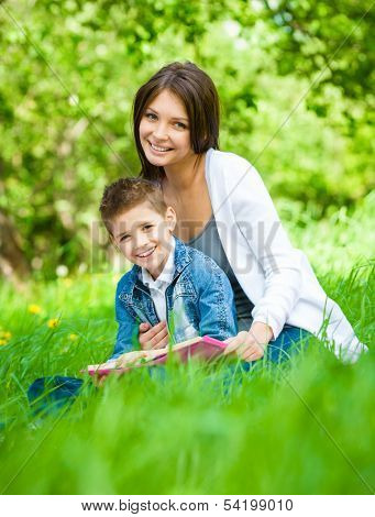 Mother and son with book sitting on green grass in green park. Concept of happy family relations and carefree leisure time