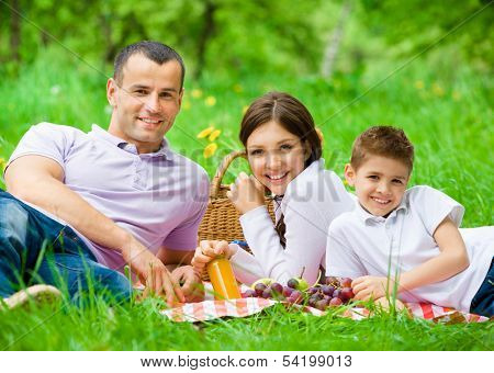 Happy family of three has picnic in park. Concept of happy family relations and carefree leisure time