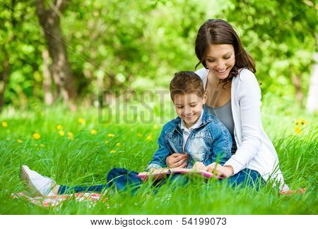 Mother and son with book sitting on green grass in park. Concept of happy family relations and carefree leisure time