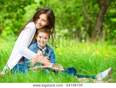 Mom and son with book sitting on green grass in green park. Concept of happy family relations and carefree leisure time