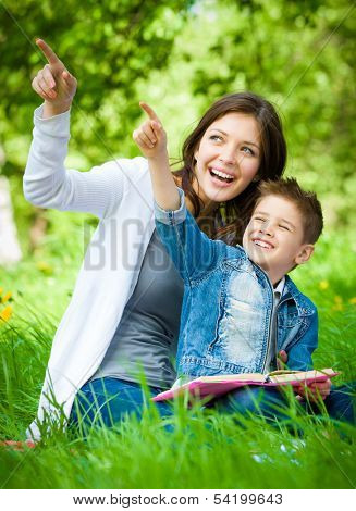 Mother and son with book sitting on green grass pointing hand gesture in park. Concept of happy family relations and carefree leisure time