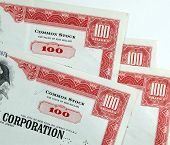 red common stock certificates of an american corporation. beautiful old documents of wealth. poster