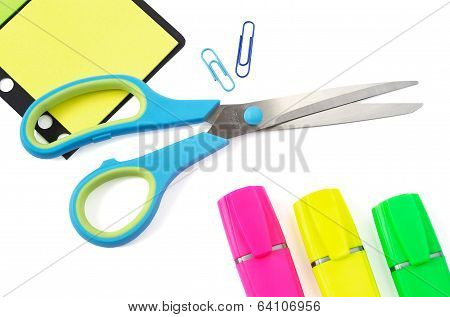 Scissor, Paper Clip, Stikers And Three Highlighter Pens On White Background