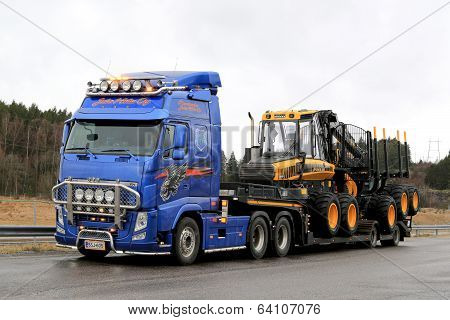 Blue Volvo FH13 Truck Hauls Ponsse Forwarder