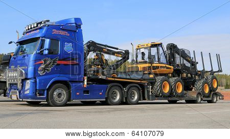 Blue Volvo FH13 Truck Hauling Ponsse Forestry Machinery