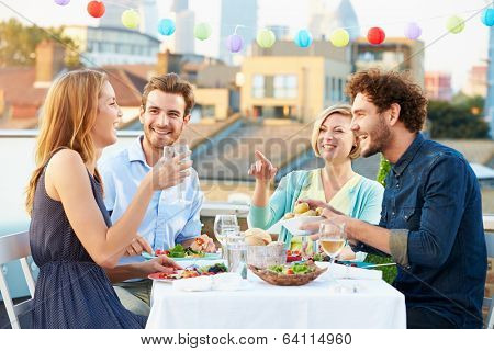 Group Of Friends Eating Meal On Rooftop Terrace