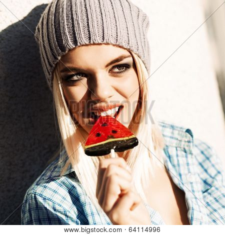Beautiful Blonde Girl In Beanie Hat With Smokey Eye Make Up Who Enjoys Licking Watermelon Lollipop
