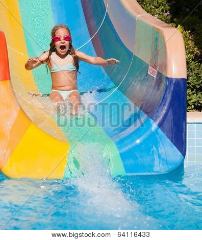 Child rolling with waterslides. Happy girl swimming