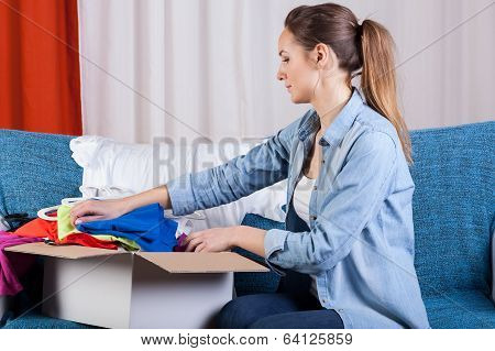 Lady Packing Clothes Into Box