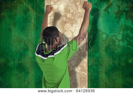 Cheering football fan in green jersey against nigeria flag in grunge effect poster