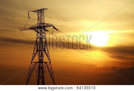 High Power Electric Line Towers At Dramatic Sunset Background