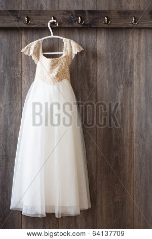 Little girls dress hanging from hook on wooden panelled wall