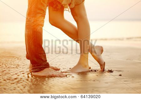 A young  loving  couple hugging and kissing on the beach at sunset. Two lovers, man and woman barefoot near the water. Summer in love
