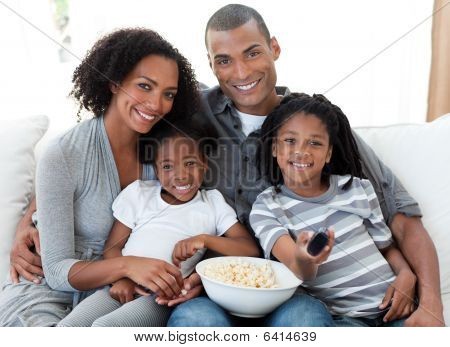 Afro-American family watching television and eating popcorn at home poster