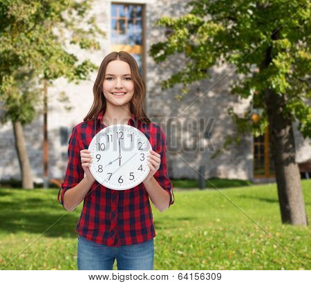 happiness and people concept - smiling young woman in casual clothes with wall clock showing 8 oclock