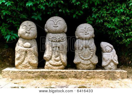 Four playful Stone Buddhist Statues In Arashiyama, Japan