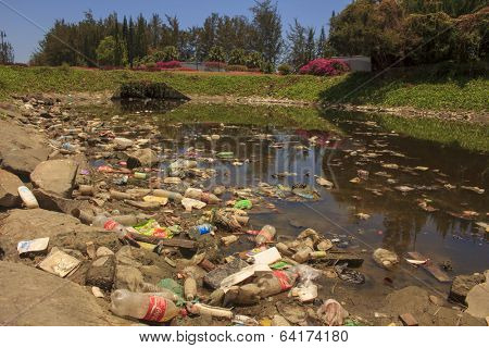 KOTA KINABALU, MALAYSIA - APRIL 26 2014: Plastic rubbish pollution in park pond. Photo showing pollution problem of litter building up in park pond due to no recycling or garbage collection services.