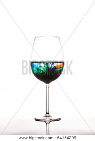 Glass With Multicolored Water On White Background
