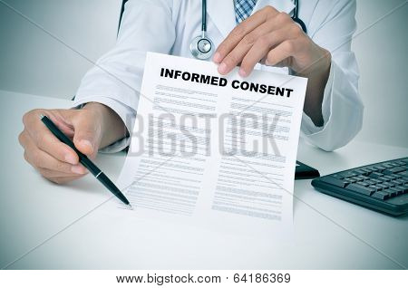 a doctor in his office showing an informed consent document and pointing with a pen where the patient must to sign