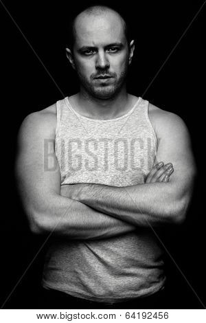 Vertical portrait of serious guy with crossed arms looking at camera