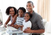 Happy young Afro-American family working with a computer at home poster