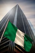 Nigeria national flag against low angle view of skyscraper poster