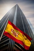 Spain national flag against low angle view of skyscraper poster