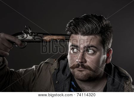Self-murderer with old pistol at his temple, close-up portrait