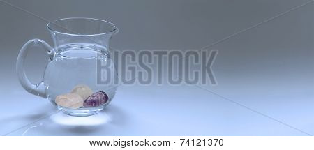 Wide blue graduated banner with a jug of water holding crystal gem stones making a gem essence poster