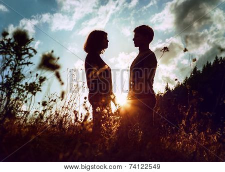 Sunrise Silouettes Of Two Inlove Young People