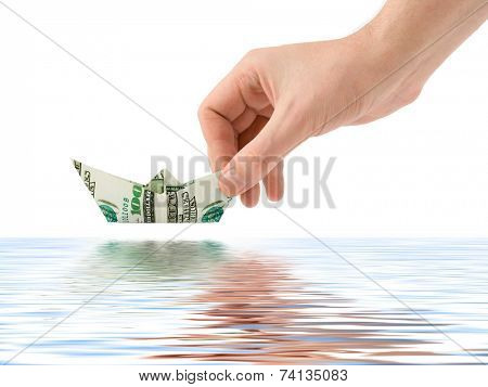 Hand launching money ship isolated on white background